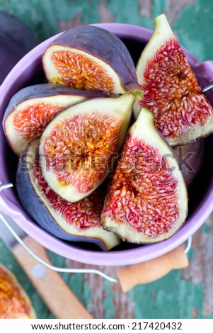 fresh figs in a bucket on wooden surface - stock photo