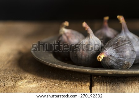 Fresh figs in moody natural lighting set with vintage style