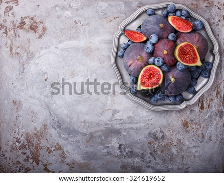 Fresh figs of different varieties and blueberries, on metal plates.Copy space.selective focus - stock photo