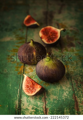 Fresh figs on green vintage wooden table - dark and moody still life - stock photo