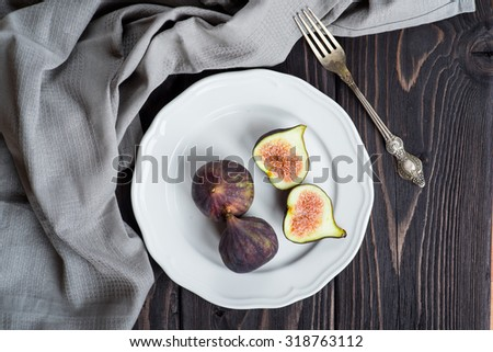 Fresh figs on white plate on rustic wooden background - stock photo