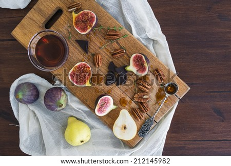 Fresh figs, pears and pecan nuts with honey on a wooden board and white tissue - stock photo