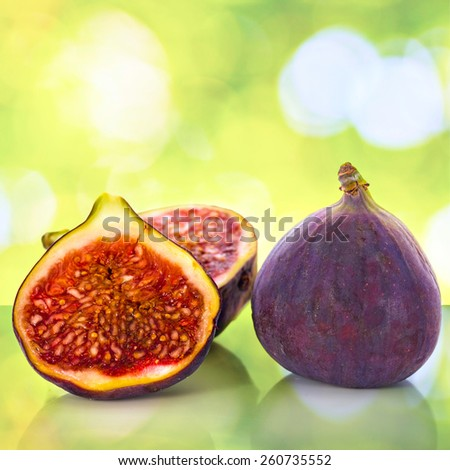 Fresh figs whole and cut isolated on colorful abstract blurred nature background - stock photo