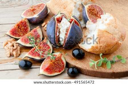 Fresh figs with cheese and honey, bread and olives on wooden table.