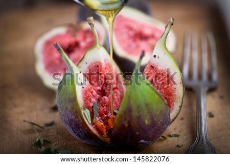 fresh figs with honey on old rustic board, ready to eat - stock photo