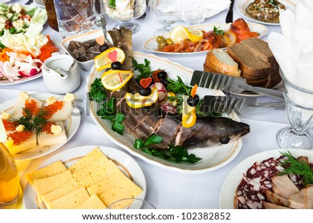 Fresh fish and snacks on holiday table - stock photo