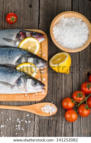 Fresh fish on chopping board with lemon and vegetables on wooden table - stock photo