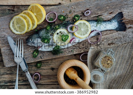 fresh fish ready to be cook on a wooden table - stock photo