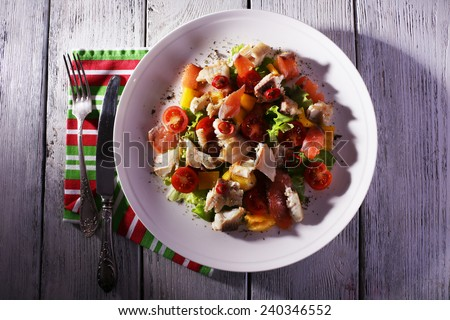 Fresh fish salad with vegetables on plate on wooden table close-up - stock photo