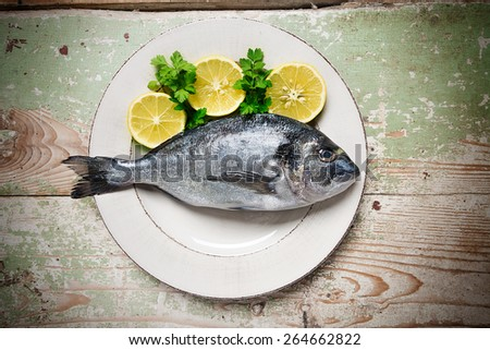 Fresh fish (Sparus aurata) with lemon and parsley on a plate served on rustic green table - stock photo