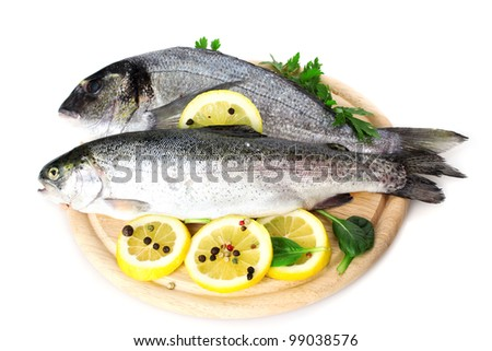Fresh fishes with lemon, parsley and spice on wooden cutting board isolated on white - stock photo
