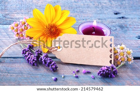 Fresh floral wellness and spa still life with spikes of scented lavender, dainty blosoms and a colourful yellow gerbera surrounding a blank gift tag with copyspace and a burning aromatherapy candle - stock photo