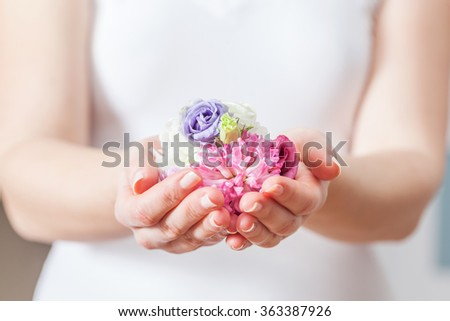 Fresh flowers in woman hand. Concept of beauty and spa, health care, aromatherapy etc. - stock photo