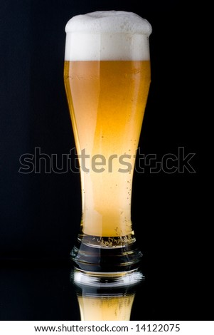 Fresh foamy beer in a glass on a black background.