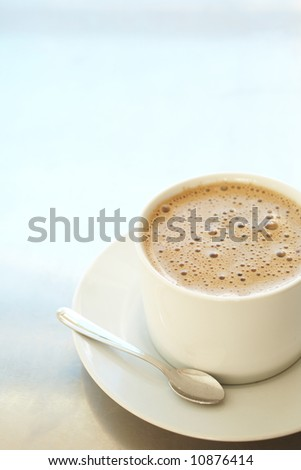 Fresh foamy cafe latte in white coffee cup on a silver background with lots of copy space Ð Shallow Depth of Field, focus on Foam - stock photo