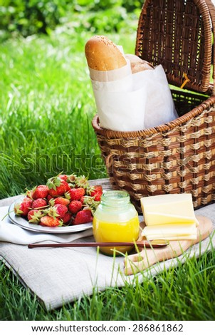 Fresh Food on Picnic. Wattled Basket on Tablecloth, Bread, Cheese, Honey, Strawberry - stock photo