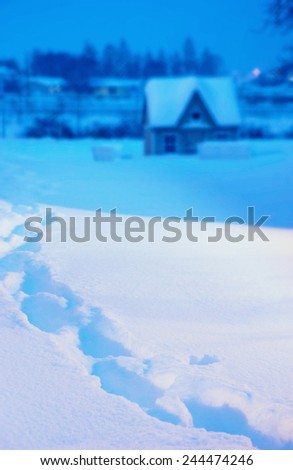 Fresh footprints in deep winter snow at twilight