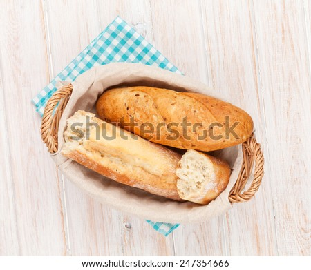 Fresh french bread in basket over white wooden table - stock photo