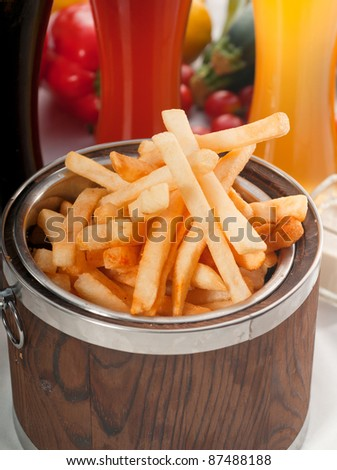 fresh french fries on a wood bucket with selection of beers and fresh vegetables on background - stock photo