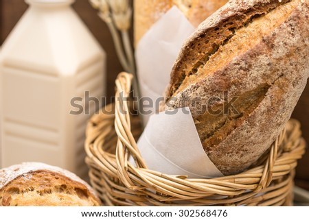 Fresh french whole wheat bread loaf wrapped in white paper in bamboo basket with bottle of milk for healthy diet - stock photo