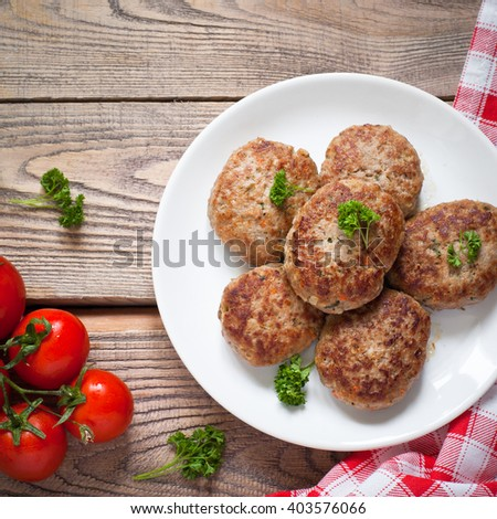 Fresh fried cutlets in a white plate on wooden table. - stock photo