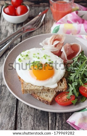 Fresh fried egg with whole grain bread , prosciutto, tomatoes and arugula. - stock photo