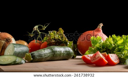Fresh fruit and vegetables on a wooden kitchen counter with tomato, cucumber, lettuce and squash or pumpkin being prepared for a healthy vegan or vegetarian diet. - stock photo