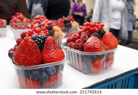 Fresh fruit berries with anonymous people in the background - stock photo