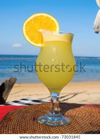 Fresh fruit cocktail on a tropical island beach - stock photo