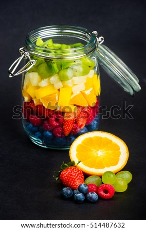 Fresh fruit in front of glass jar full of colorful fruits on black background