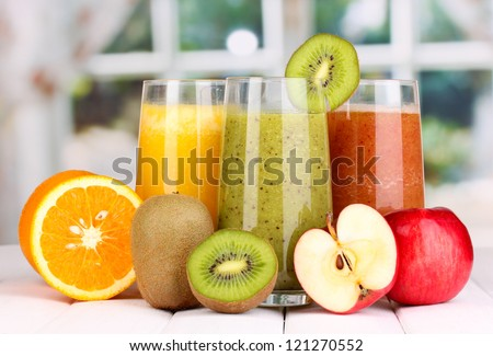 fresh fruit juices on wooden table, on window background - stock photo