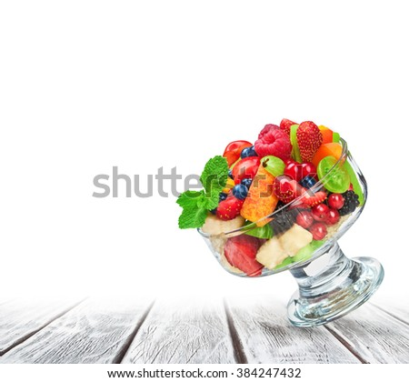 fresh fruit salad in glass bowl on white wooden background