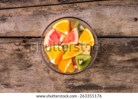 Fresh fruit salad in glass bowl. Vitamins mix on wooden table. Top view image  - stock photo