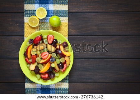 Fresh fruit salad made of grape, strawberry, plum and nectarine served on plate with lemon above, photographed overhead on dark wood with natural light - stock photo