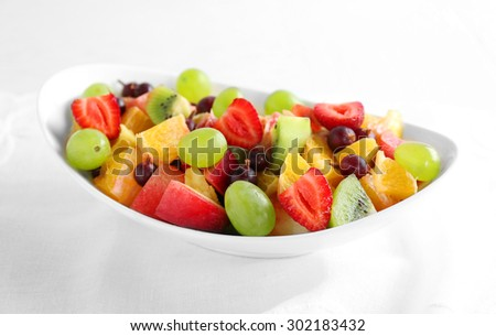 Fresh fruit salad on white wooden table - stock photo