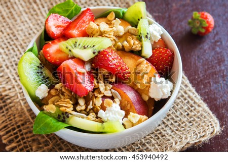 Fresh fruit salad with granola, feta cheese and honey in bowl for healthy breakfast