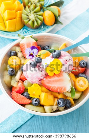 Fresh fruit salad with scoops of cherry ice cream - stock photo