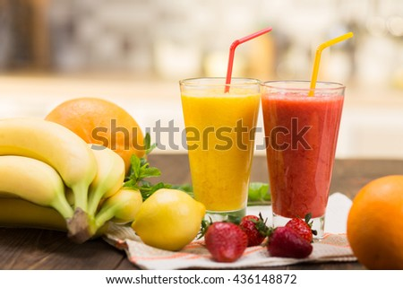 Fresh fruit smoothies on kitchen table in a two glass