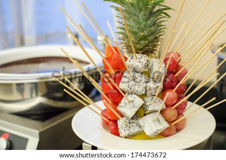 Fresh fruit with chocolate fondue in restaurant - stock photo