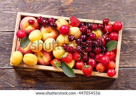 fresh fruits and berries in wooden box, top view - stock photo