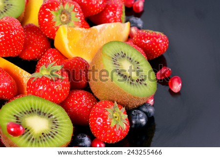 Fresh fruits and berries on a black background - stock photo