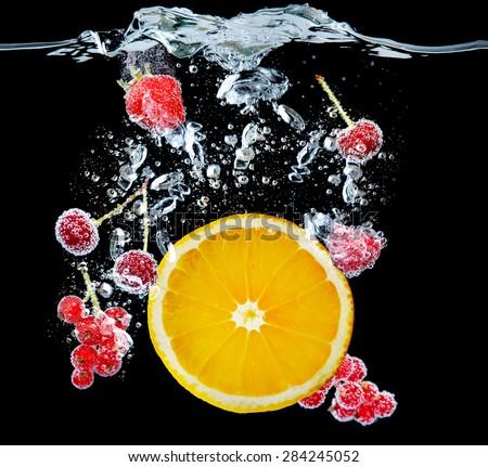 Fresh fruits and berries splashing in water on black background - stock photo