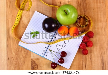 Fresh fruits and tape measure with notebook for writing notes, concept of slimming, diet and healthy nutrition - stock photo