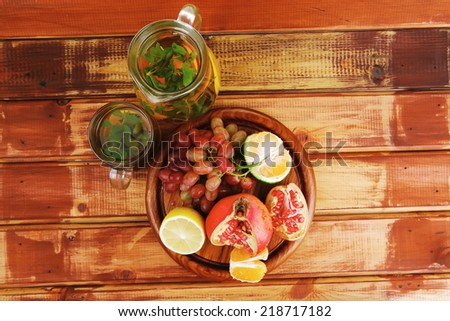 fresh fruits and tea on wooden table - stock photo