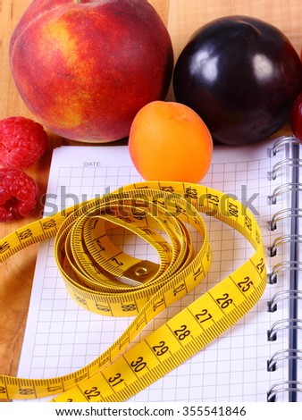 Fresh fruits and vegetables with tape measure on notebook for writing notes, concept of slimming, diet and healthy nutrition - stock photo