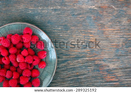 fresh fruits background with raspberries on rustic wooden table - stock photo