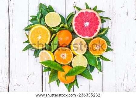 Fresh fruits heart on white wood background.Mixed citrus fruits still life. - stock photo