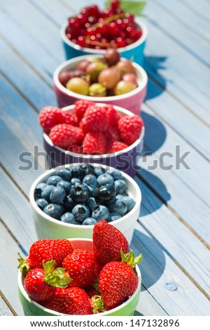 Fresh fruits in fruit bowls on wooden background - stock photo