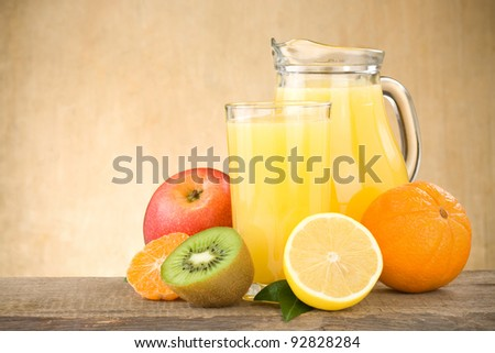 fresh fruits juice in glass and slices on wood background