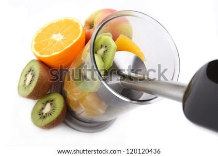 Fresh fruits mixing with hand blender - stock photo